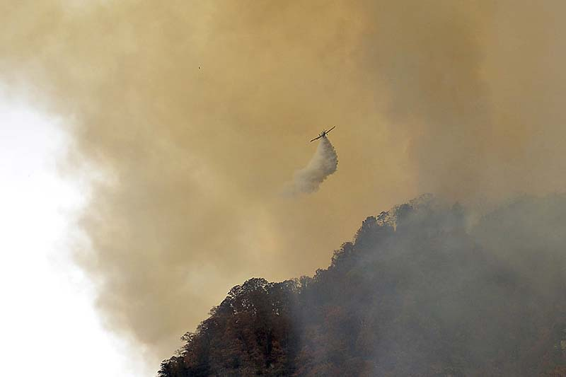Crews work a wildfire near Lake Lure Friday, on November 11, 2016. State transportation officials say the wildfire near Lake Lure has forced the immediate closing of US 64/74A and NC 9 in Rutherford County. Photo: The Times via AP
