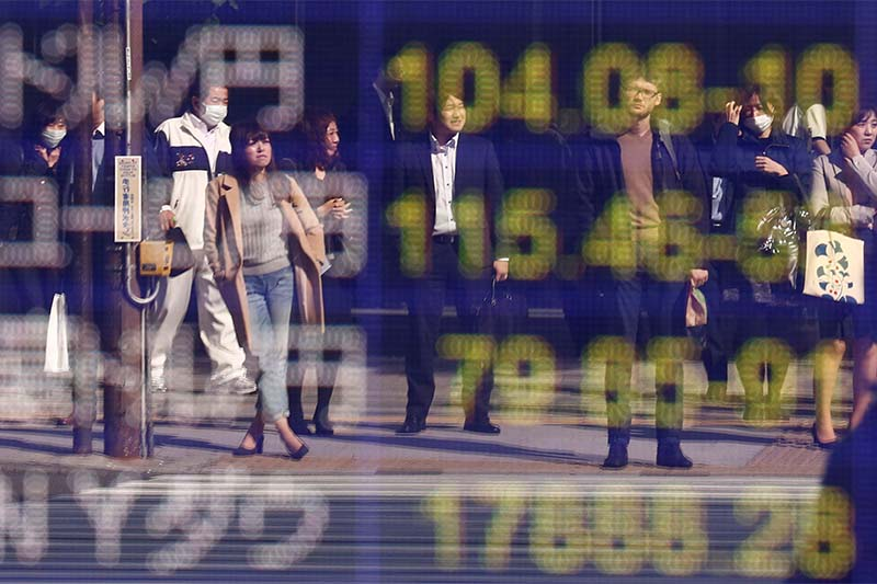 People are reflected in a display (top) showing the current exchange rate between US dollar and Japanese Yen outside a brokerage in Tokyo, Japan, on November 7, 2016. Photo: Reuters