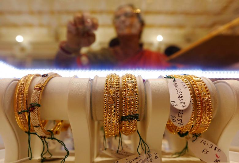 Gold bangles are on display as a woman makes choices at a jewellery showroom during Dhanteras, a Hindu festival associated with Lakshmi, the goddess of wealth, in Kolkata, October 28, 2016. REUTERS/Rupak De Chowdhuri