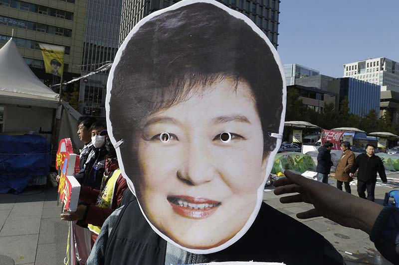 A South Korean protester wears a mask of South Korean President Park Geun-hye during a rally calling for Park to step down in downtown Seoul, South Korea, on Friday, November 11, 2016. Photo: AP