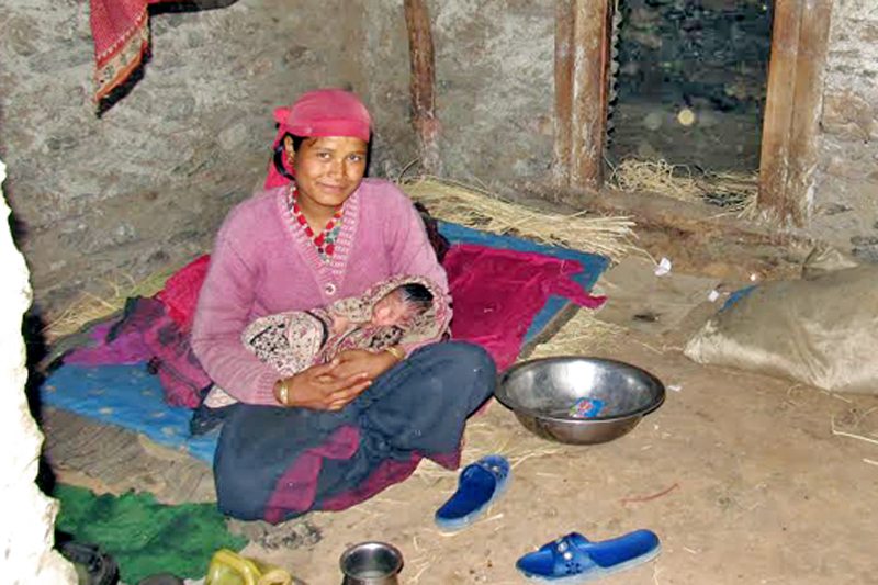 A woman cradles her newborn child in a cowshed, in Bajura, on Saturday, December 17, 2016. Photo: THT