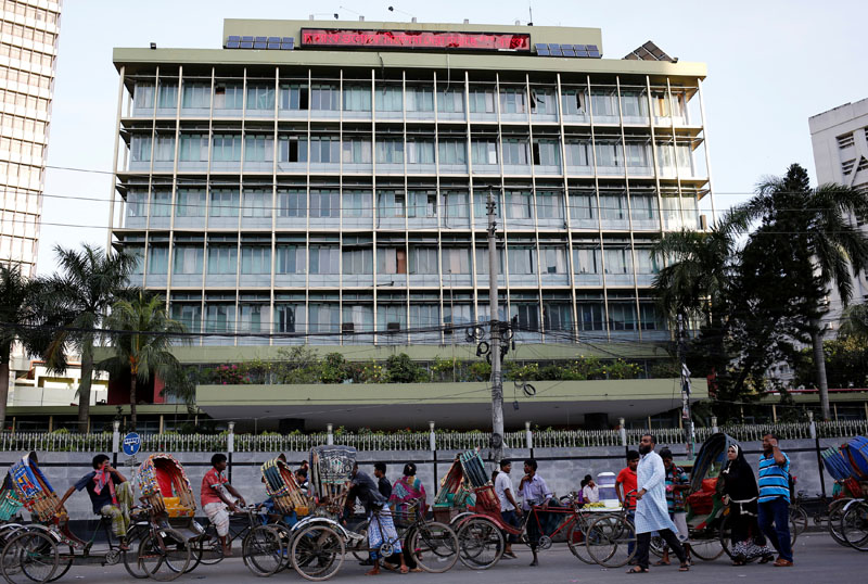 Commuters walk in front of the Bangladesh central bank building in Dhaka, Bangladesh, on September 30, 2016. Photo: Reuters