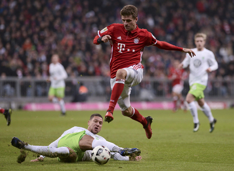 Bayern Munich's Thomas Mueller and Wolfsburg's Jeffrey Bruma in action. Photo: Reuters
