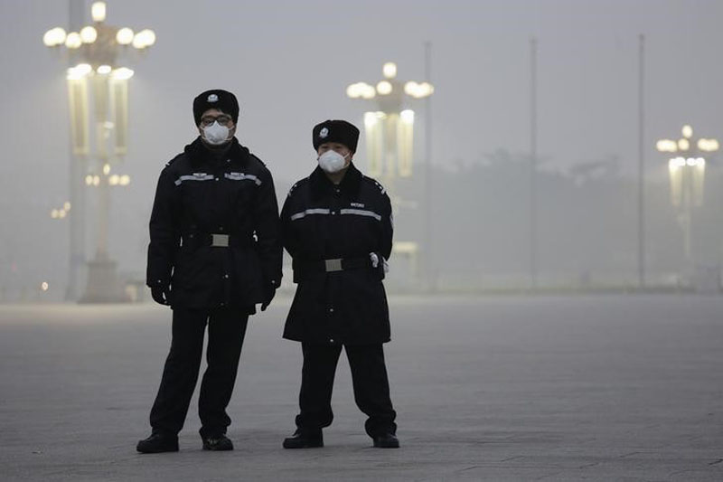 File - Policemen wear protective masks at the Tiananmen Square on an extremely polluted day as hazardous, choking smog continues to blanket Beijing, China, on December 1, 2015. Photo: Reuters