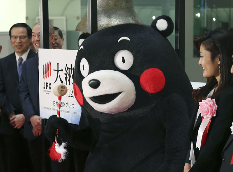 Kumamon, the popular black bear mascot of Japan's Kumamoto Prefecture, poses for photographers before ringing the closing bell as four-time Olympic wrestling champion Kaori Icho (right) smiles during a ceremony of the last trading day at the Tokyo Stock Exchange in Tokyo, on Friday, December 30, 2016. Photo: AP