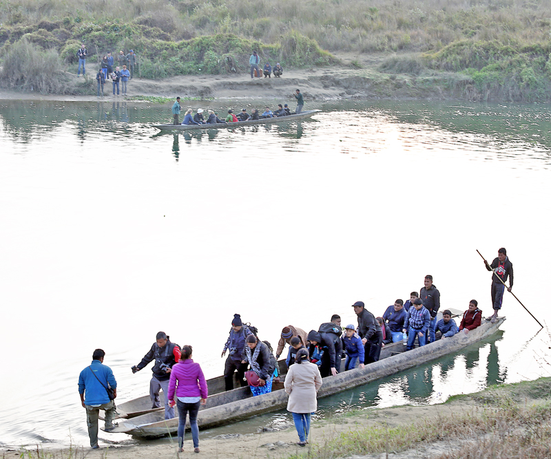 Tourists prepare to board a handmade boat in the Rapti River in Sauraha of Chitwan district, on Friday, December 30, 2016. Photo: RSS