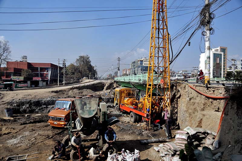 Labourers are seen constructing a new bridge over Dhobikhola along the Maitighar-Tinkune road section at Bijulibazaar of Kathmandu, on Saturday, December 31, 2016. Photo: RSS