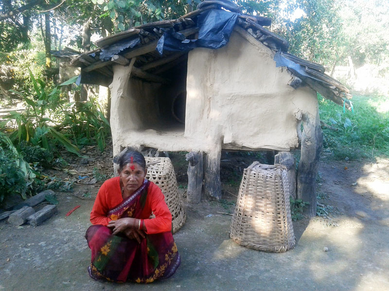 A woman sits near chhaupadi shed in Amarpur of Kanchanpur district, on Saturday, December 24, 2016. It is a local custom to keep the menstruating women isolated in chhaupadi shed. Photo: RSS