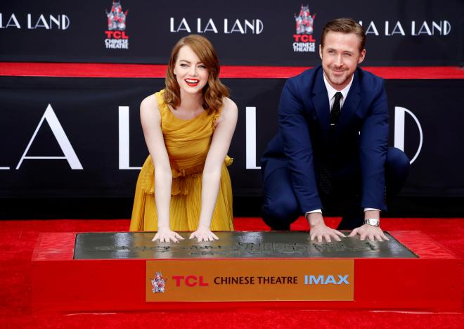 Actors Emma Stone and Ryan Gosling place their handprints in cement during a ceremony in the forecourt of the TCL Chinese theatre in Hollywood, California U.S., December 7, 2016.   REUTERS/Mario Anzuoni