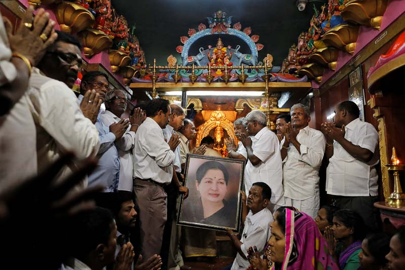 Well wishers of Tamil Nadu Chief Minister Jayalalithaa Jayaraman hold her portrait as they pray at a temple in Mumbai, India, on Monday, December 5, 2016. Photo: Reuters