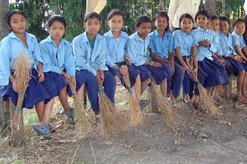 Students of the Mahamai Basic School in Golakharka of Ilam district pose for a photograph with brooms as they launch a clean-up campaign, on Monday, December 12, 2016. Photo: RSS