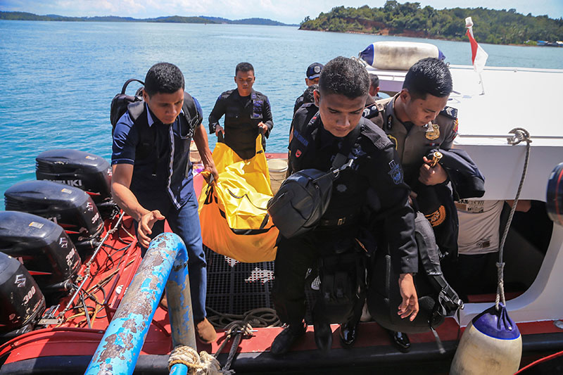 Police carry a body bag containing debris and belongings recovered from an aircraft carrying 13 police personnel which went missing on Saturday in Batam, Riau Islands, Indonesia, on December 4, 2016 in this photo taken by Antara Foto.  Photo: Antara Foto via Reuters