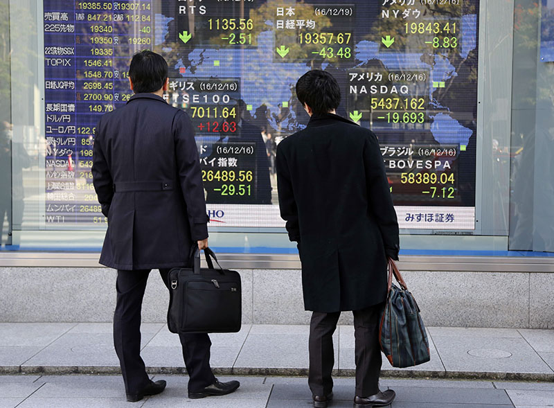 People look at an electronic stock board of a securities firm in Tokyo, on Monday, December 19, 2016. Photo: AP