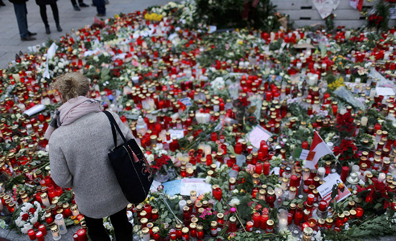 A woman stands in front of flowers and candles, placed near the Christmas market at Breitscheid square in Berlin, Germany, on December 23, 2016, following an attack by a truck which ploughed through a crowd at the market on Monday night. Photo: Reuters