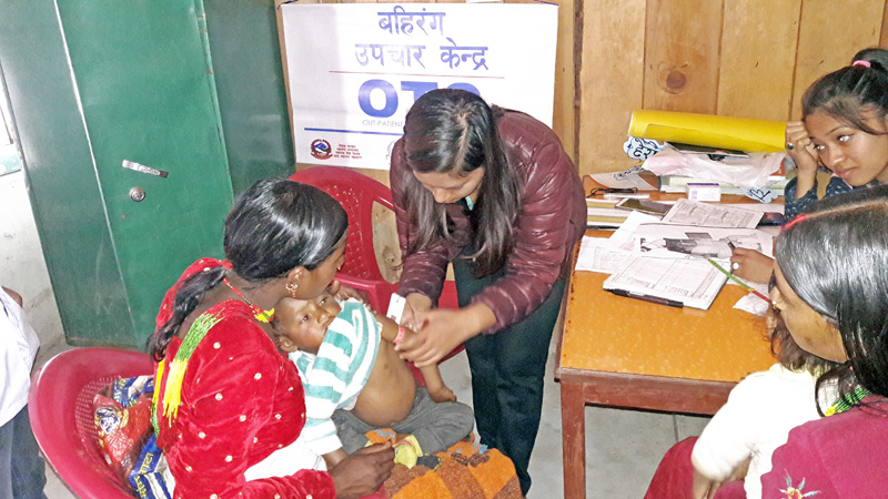 A health worker examining a child suffering from malnutrition in Martadi, Bajura, on Wednesday. The health check up was organised by the Integrated Rural Health Development Training Centre Nepal in coordination with the Ministry of Health. Photo: THT