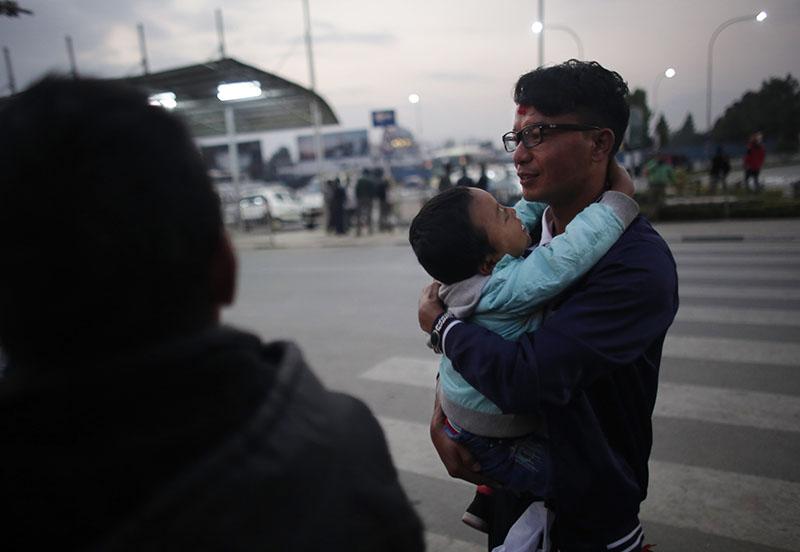 In this Monday, November 28, 2016 photo, a Nepali migrant worker Krishna Bahadur Tamang, carries his son before departing for Qatar at Tribhuwan Internation airport in Kathmandu. Photo: AP