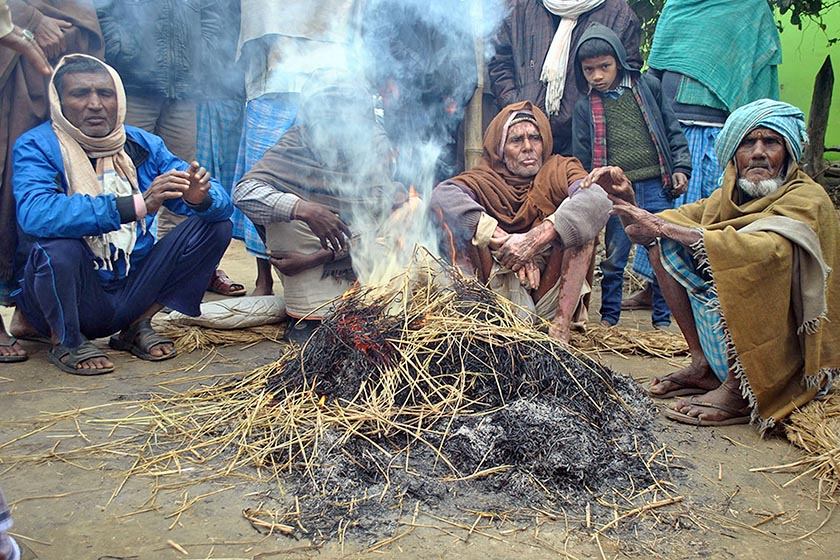People burn hay to keep themselves warm in Udayapurghurmi of Parsa district on Saturday, December 10. Cold wave has affected general life in the district for some days. Photo: RSS
