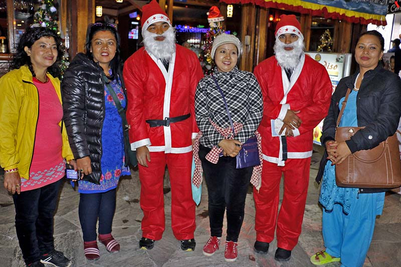 People pose for a photograph with Santa Clauses on the occasion of Christmas at Lake Side in Pokhara, on Sunday, December 25, 2016. Photo: RSS
