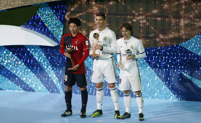 Real Madrid's Cristiano Ronaldo celebrates with the Golden Ball trophy, Real Madrid's Luka Modric with the Silver Ball trophy and Kashima Antlers' Gaku Shibasaki with Bronze Ball trophy