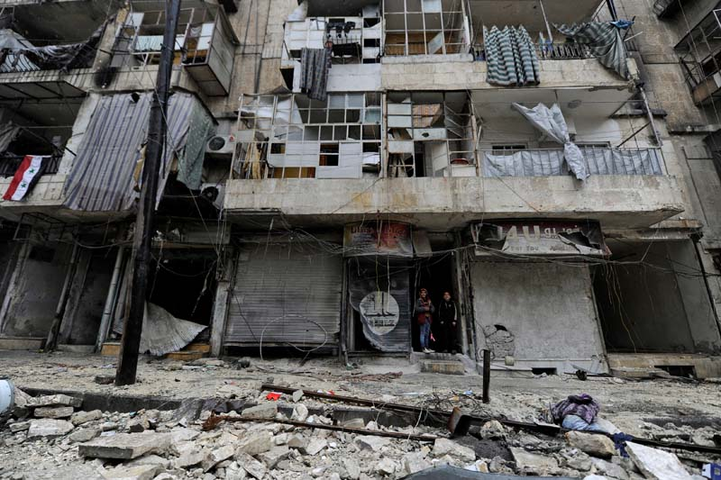 Boys stand amid the damage in the government-held al-Shaar neighborhood of Aleppo, during a media tour, Syria, on December 13, 2016. Photo: Reuters