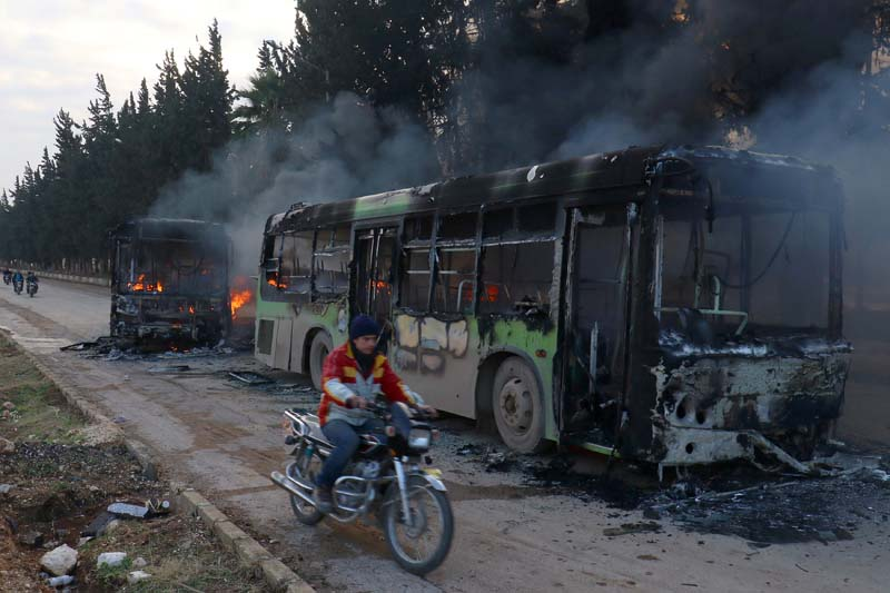 A man on a motorcycle drives past burning buses while en route to evacuate ill and injured people from the besieged Syrian villages of al-Foua and Kefraya, after they were attacked and burned, in Idlib province, Syria, on Sunday, December 18, 2016. Photo: Reuters