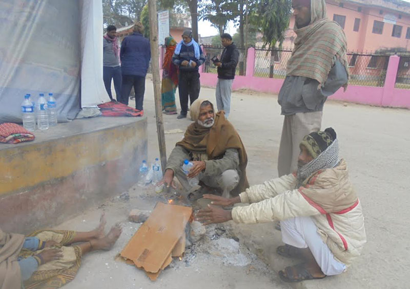 Locals warming themselves near a fire after the cold increased, in  Rajbiraj, Saptari, on Sunday, December 11, 2016.  The dip in temperature has affected life in the district. Photo: THT