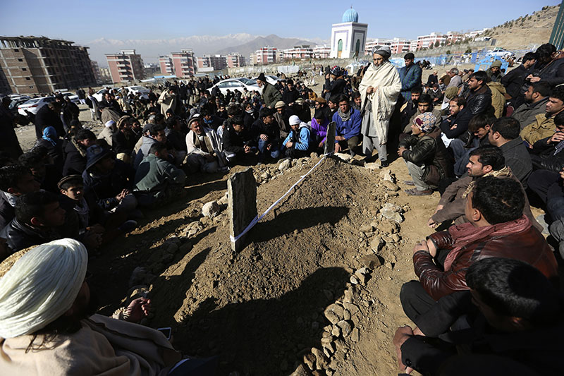 Villagers pray in front of the grave of a victim of Tuesday's two bombings in Kabul, Afghanistan, on Wednesday, January 11, 2017. Photo: AP
