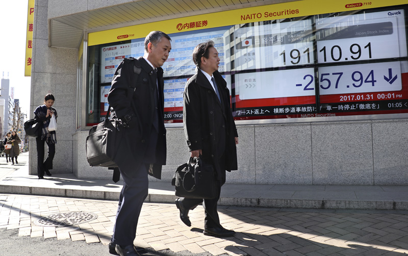 Men walk past an electronic stock indicator of a securities firm in Tokyo, Tuesday, Jan. 31, 2017. Photo: AP