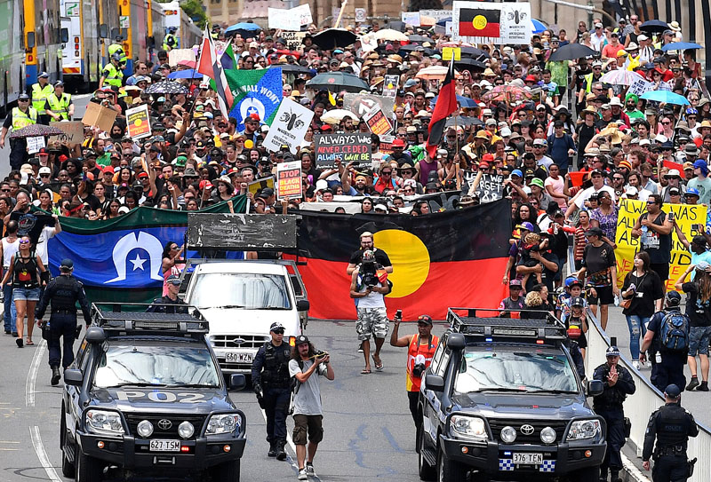 Police escort people joining a march with Aboriginal protesters on Australia Day in central Brisbane, Australia, on January 26, 2017. Photo: Reuters