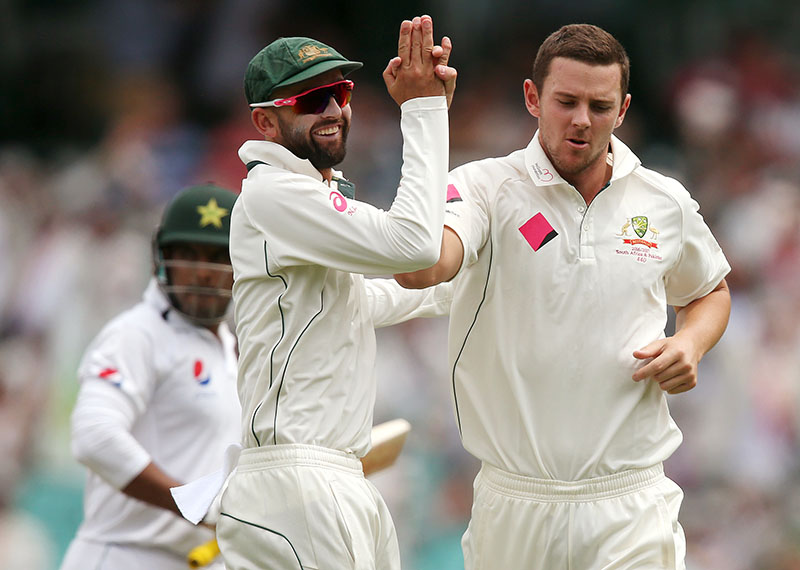 Pakistan's Sharjeel Khan (left) watches as Australia's Josh Hazlewood (right) is congratulated by terammate Nathan Lyon after taking Khan's wicket during their cricket test match in Sydney, Australia, on Wednesday, January 4, 2017. Photo: AP