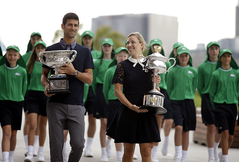 Defending men's and woman's champions Serbia's Novak Djokovic (left) and Germany's Angelique Kerber carry their trophies to the official draw ceremony ahead of the Australian Open tennis championships in Melbourne, Australia, Friday, Jan. 13, 2017. (AP Photo/Mark Baker)