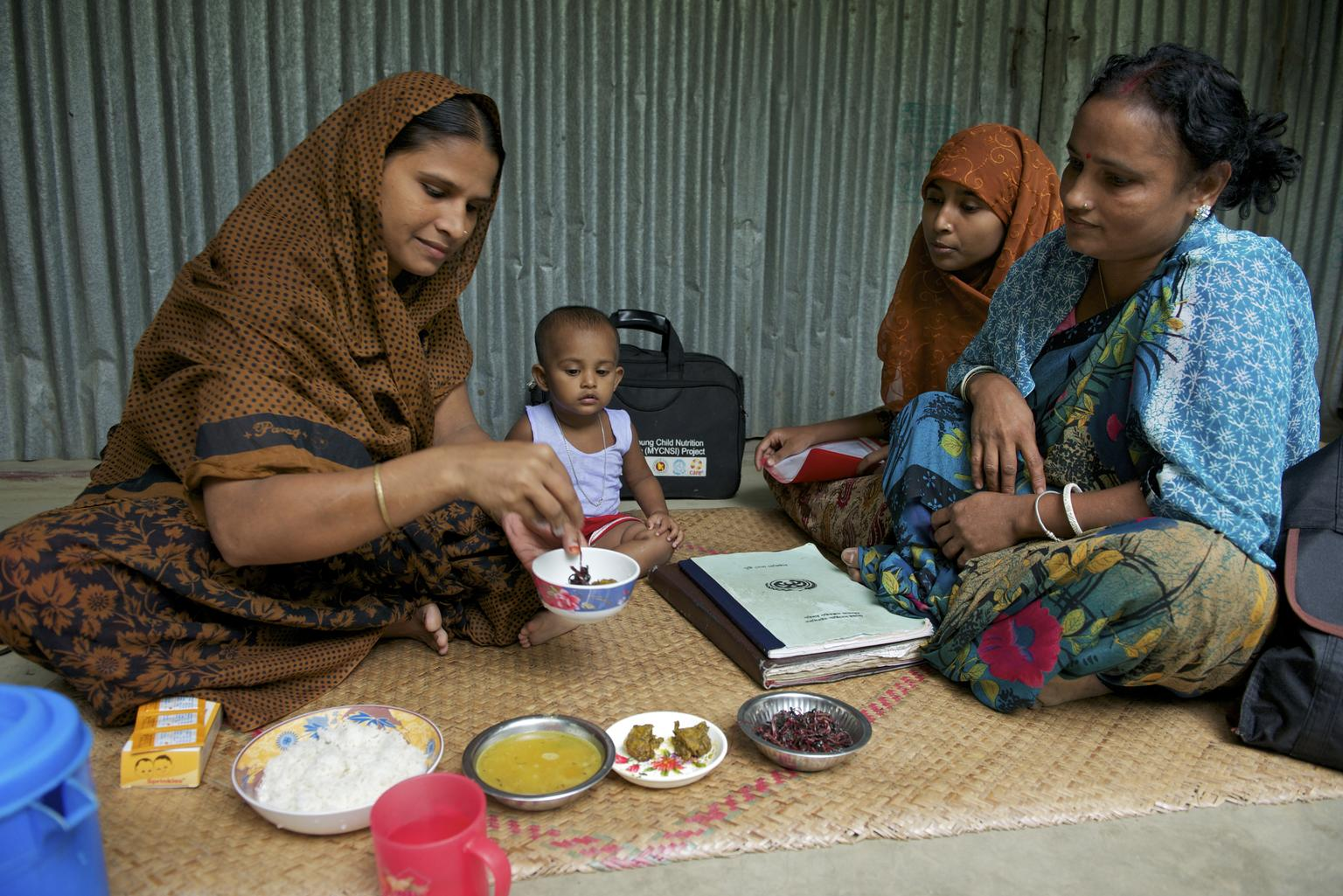 File Photo - Accompanied by a health worker, Chaya Rani (left) adds Sprinkles, a micronutrient powder (MNP), to food for her 15-month-old daughter, Nishimoni, at home in Sharisha Bari Village in the north-western district of Jamalpur, Dhaka Division. u00a9 UNICEF/NYHQ2012-1962/Noorani