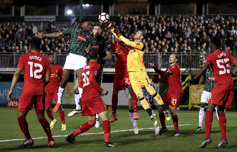 Plymouth Argyle's Yann Songo'o (top left) and Liverpool goalkeeper Loris Karius battle for the ball during their English FA Cup, third round replay match against Plymouth Argyle at Home Park, Plymouth, England, on Wednesday, January 18, 2017. Photo: Andrew Matthews/PA via AP