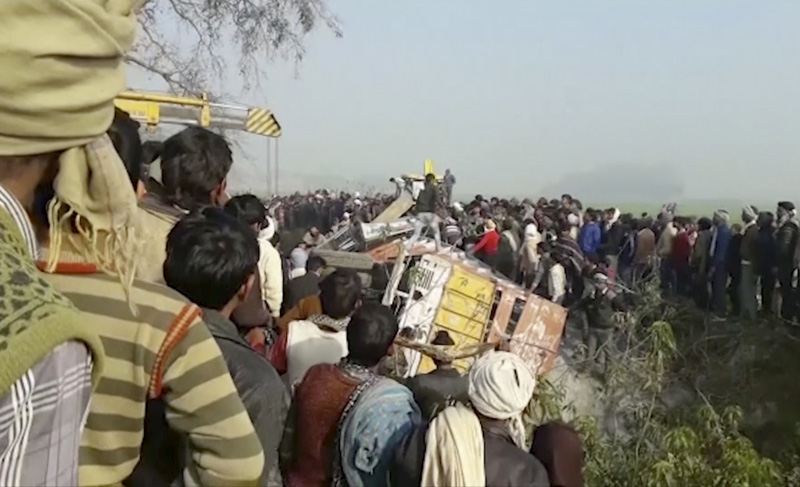 In this image from video, people gather at the site where a truck loaded with sand collided with a school bus in the northern Indian state of Uttar Pradesh Thursday, Jan. 19, 2017. Photo: AP