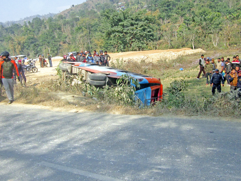 Locals gather to observe the wreckage of a bus that skidded off the road at Amreni along the Prithvi Highway in Byas Municipality of Tanahun district, on Wednesday, January 18, 2017. Photo: Madan Wagle