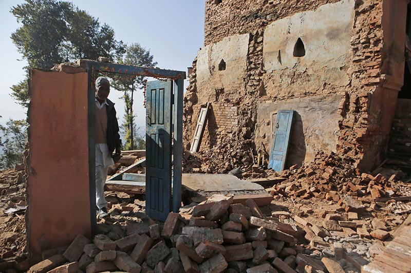 In this Nov. 22, 2016 photo, Chandra Lal Bhadal, the priest of Changu Narayan temple, stands in the debris of his house that was destroyed in a 2015 earthquake. Photo: AP