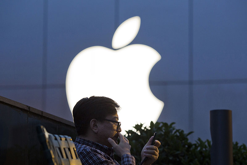 FILE - A man uses his mobile phone near an Apple store logo in Beijing, China. Apple Inc. has filed suit in China challenging Qualcomm Incu2019s fees for technology used in smartphones two years after Chinese regulators fined the chipmaker for its licensing practices, on May 13, 2016. Photo: AP