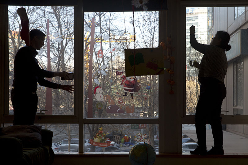 Yann Boquillod (left) founder of start-up AirVisual, uses a device to test the air coming through a gap in the window as a worker uses tape to seal other gaps at the Ivy Bilingual School in Beijing, on January 13, 2017. Photo: AP
