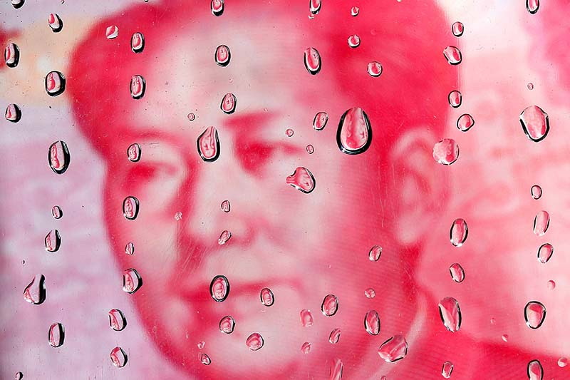 File-A portrait of former Chinese leader Mao Zedong on a yuan banknote is reflected in water droplets in this picture illustration taken in Taipei on October 8, 2010. Photo: Reuters