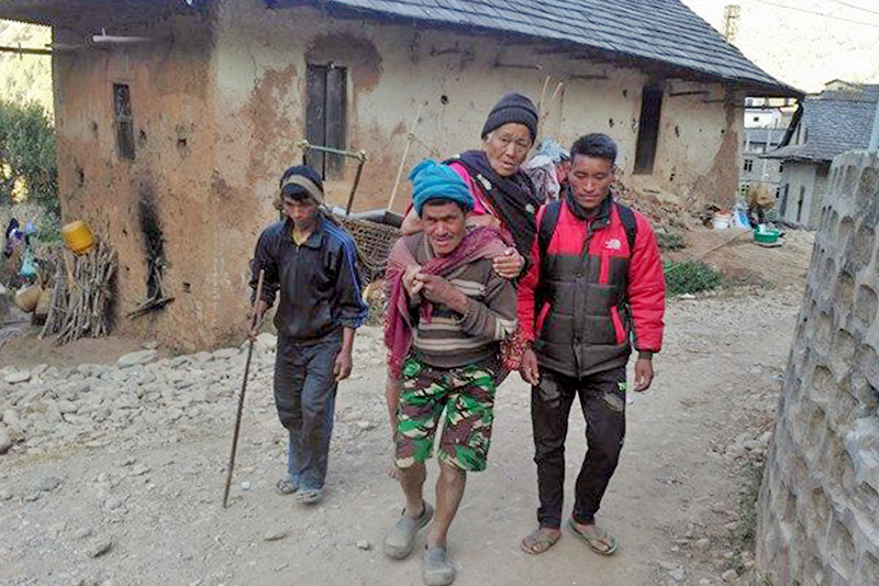 An unwell elderly woman is being carried on back of a person due to lack of transportation to reach the district headquarters Dunai of Dolpa district for treatment, on Friday, January 27, 2017. Photo: RSS