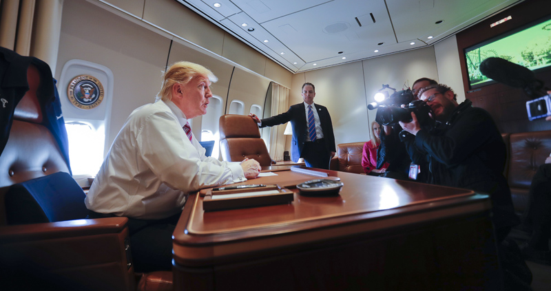 President Donald Trump sits at his desk on Air Force One upon his arrival at Andrews Air Force Base, Md., Thursday, Jan. 26, 2017. Photo: AP