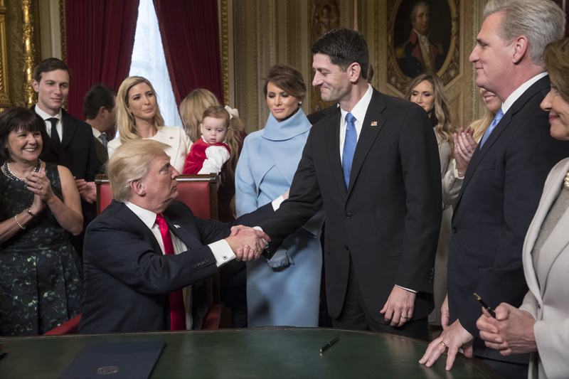President Donald Trump turns to House Speaker Paul Ryan as he is joined by the Congressional leadership and his family as he formally signs his cabinet nominations into law, in the President's Room of the Senate, at the Capitol in Washington, Friday, Jan. 20, 2017. Photo: AP