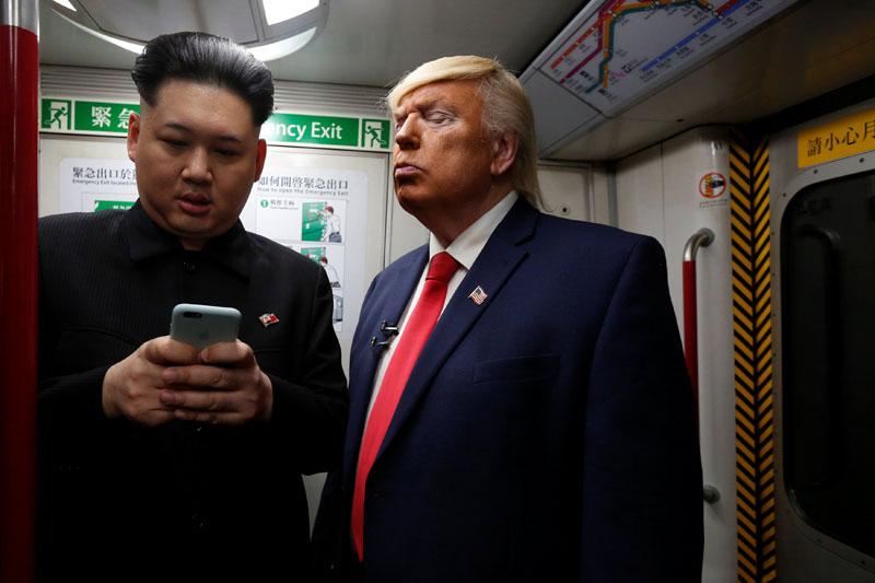 Howard (37) an Australian-Chinese who is impersonating North Korean leader Kim Jong-un, and Dennis Alan of Chicago (66) who is impersonating US President Donald Trump, ride a subway train in Hong Kong, China, on January 25, 2017. Photo: Reuters