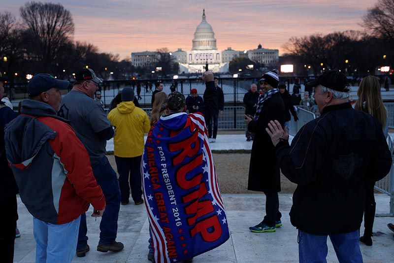 Supporters of U.S. President-elect Donald Trump gather in the foreground of the U.S. Capitol on the National Mall before Trump is to be sworn in in Washington U.S., January 20, 2017. REUTERS/Shannon Stapleton