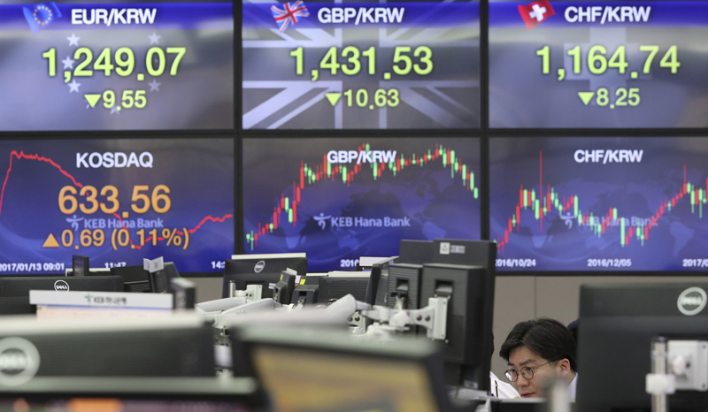 A currency trader watches monitors near screens showing foreign exchange rates at the foreign exchange dealing room in Seoul, South Korea, Friday, Jan. 13, 2017. Photo: AP