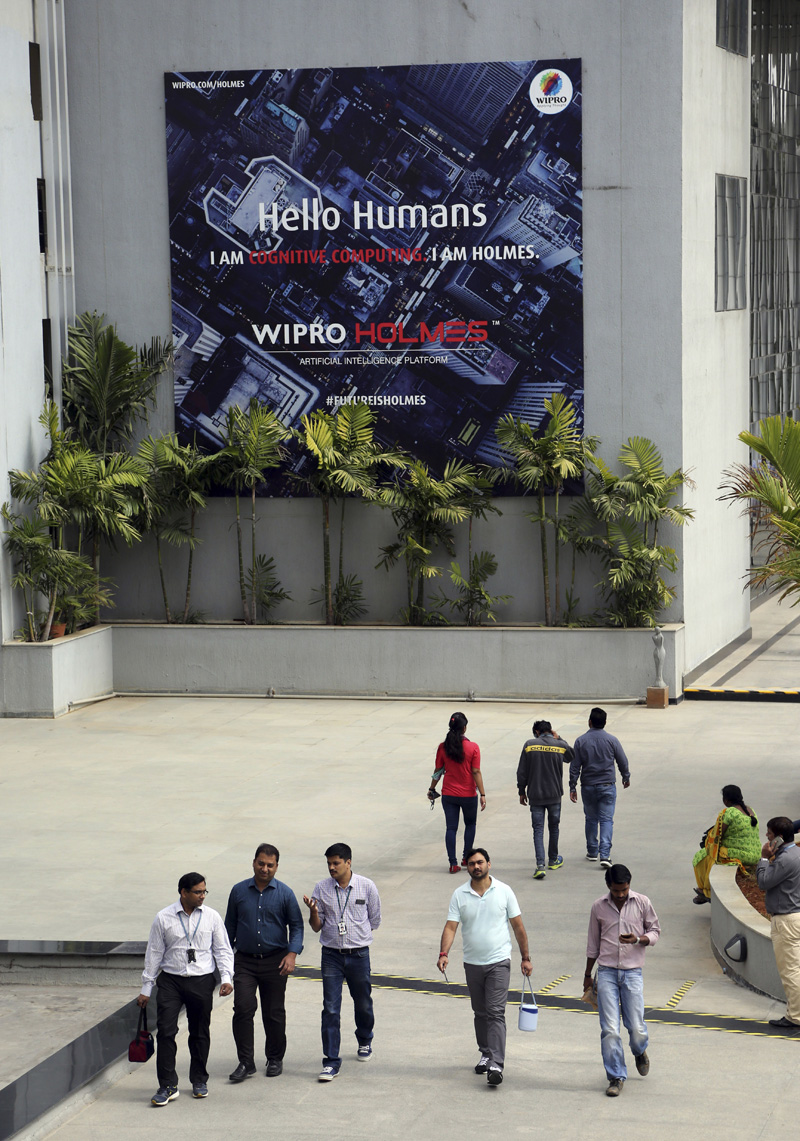 FILE- In this Jan. 18, 2016 file photo, Wipro Ltd. employees walk inside the company's compound during a break at their headquarters in Bangalore, India. Photo: AP