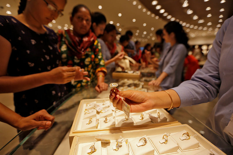 File - A sales person shows a gold ring to customers at a jewellery showroom during Dhanteras, a Hindu festival associated with Lakshmi, the goddess of wealth, in Ahmedabad, India, on October 28, 2016. Photo: Reuters