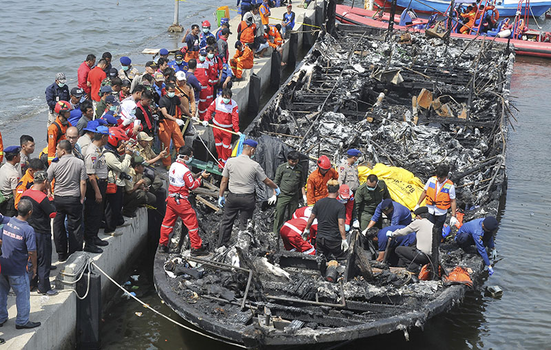 Rescuers search for victims from the wreckage of a ferry that caught fire off the coast of Jakarta after it was docked at Muara Angke Port in Jakarta, Indonesia, on Sunday, January 1, 2017. Photo: AP