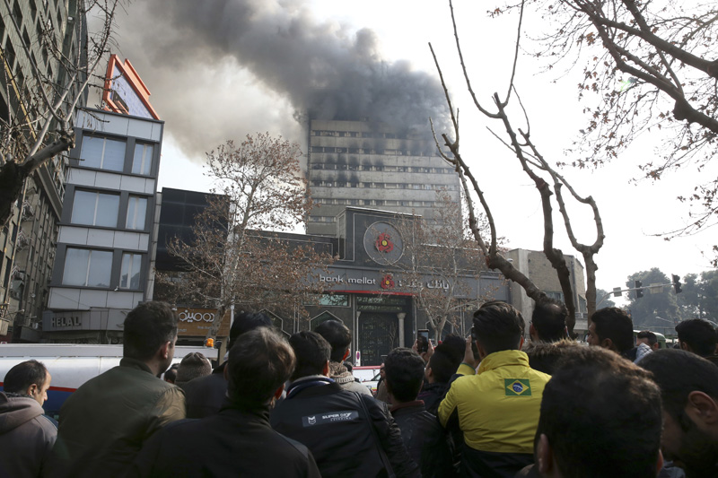 Iranians watch the Plasco building where smoke rises from its windows in central Tehran, Iran, Thursday, Jan. 19, 2017. Photo: AP