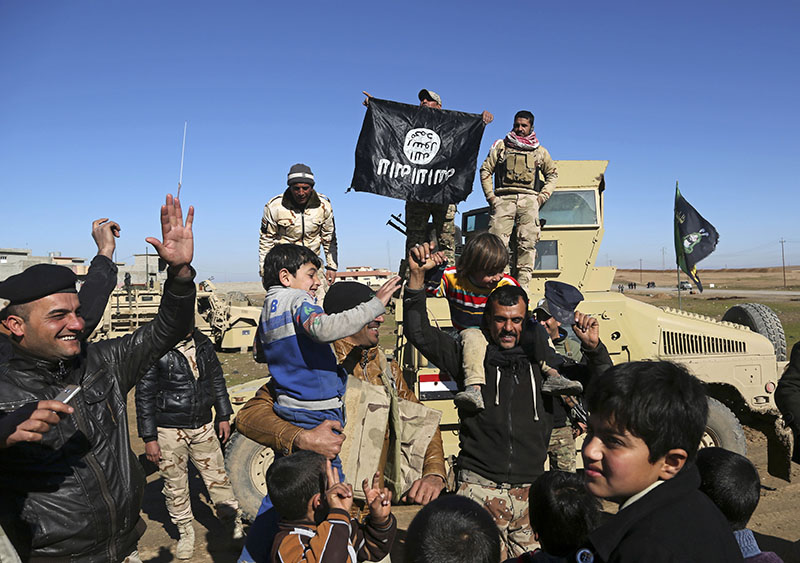 File - Iraqi Army soldiers celebrate with residents of liberated neighborhoods as they hold upside down a flag of the Islamic State group, in the eastern side of Mosul, Iraq, on Tuesday, January 24, 2017. Photo: AP
